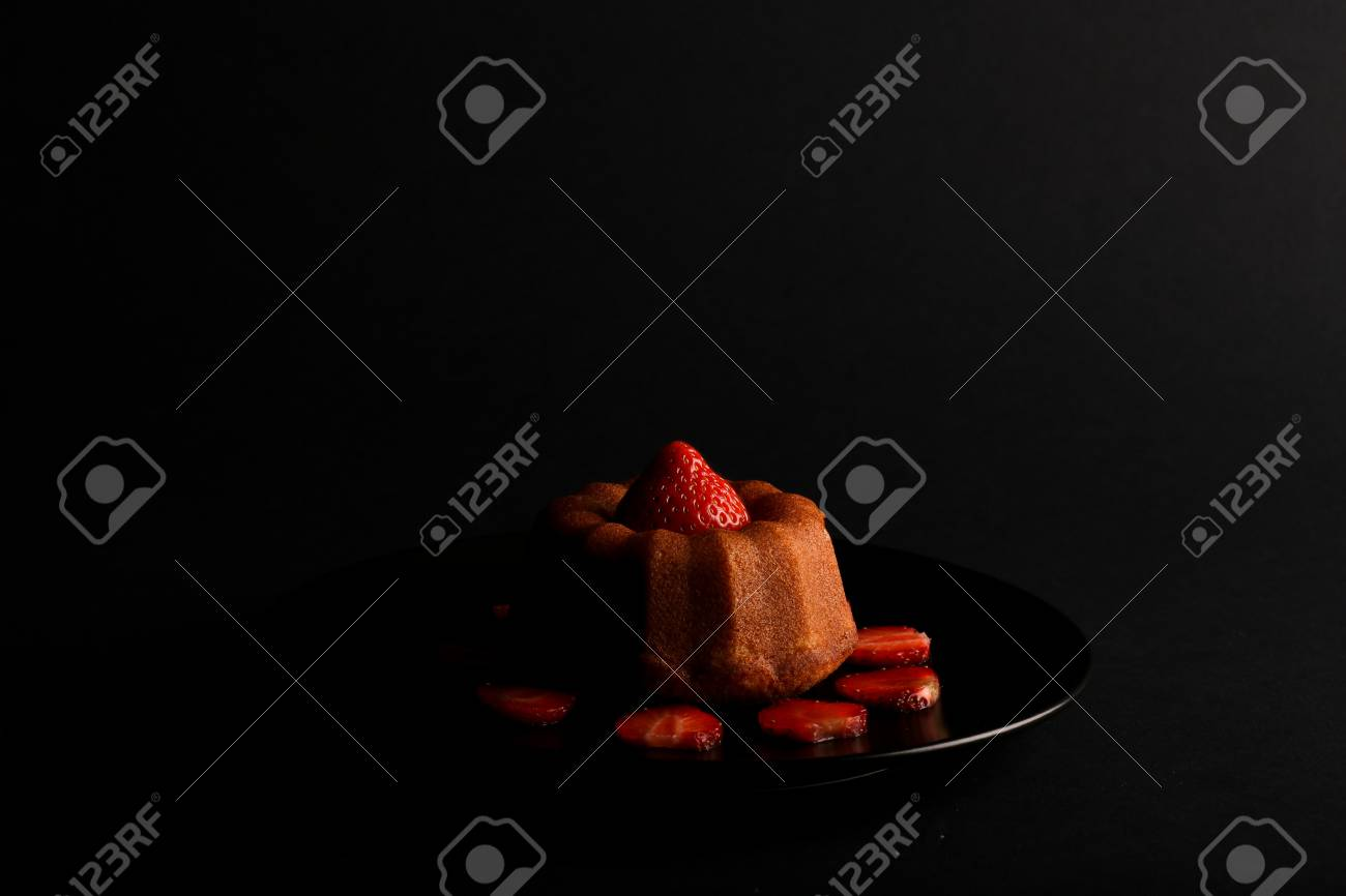 Lemon vanilla mini pound  bundt  cake with strawberry on top and sliced strawberries on black plate and dark background Stock Photo - 20889885