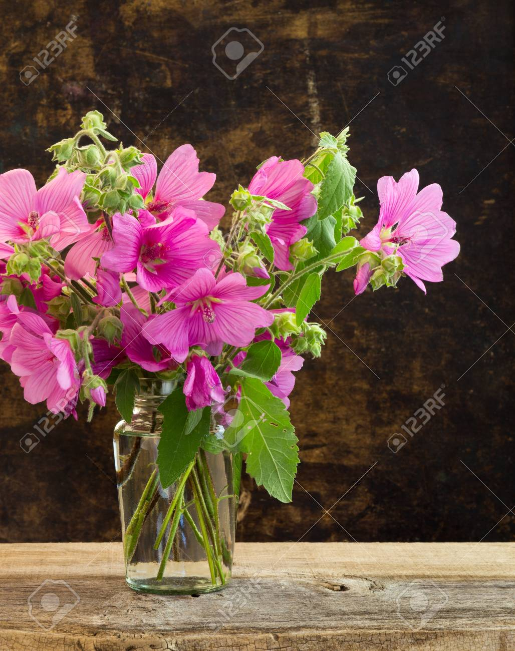 Pink Hibiscus Flowers Bouquet In A Vase On Dark Rustic Background