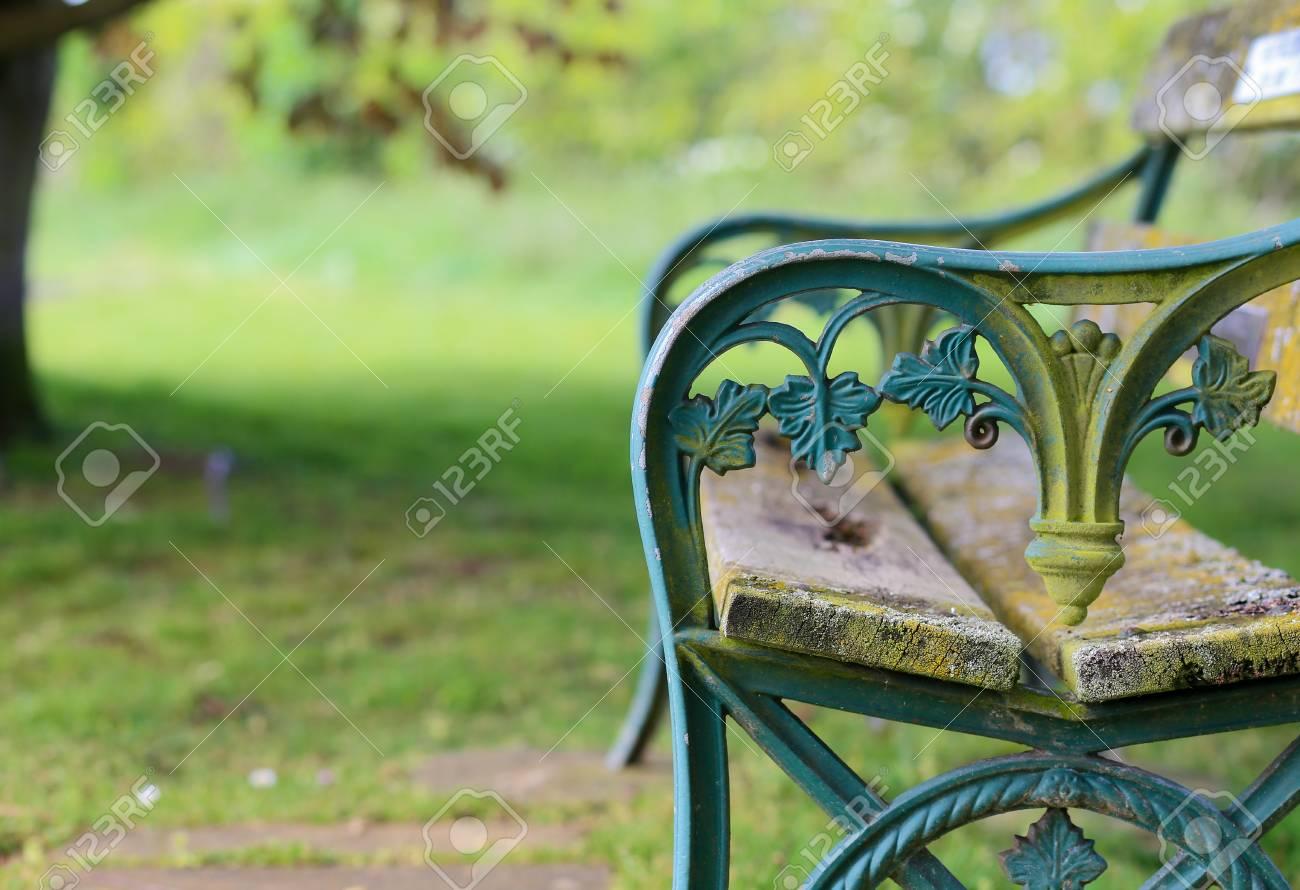 Vieux Banc De Jardin vieux banc de jardin en fonte peint bleu turquoise avec des planches de  bois patinés, fond vert flou