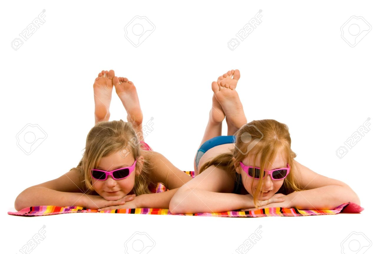young feet Stock Photo - Two young girls lying in the sun on a towel