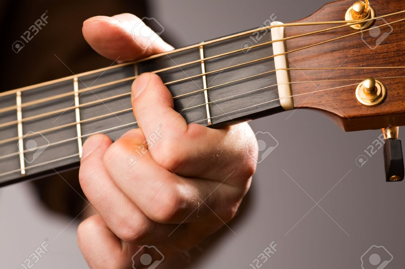 Close Up Of Acoustic Guitar Players Left Hand Fingering A Chord