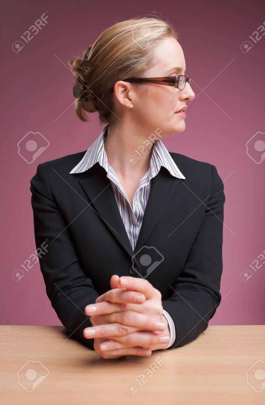 Newsreader sitting at desk with hands clasped Stock Photo - 6683353