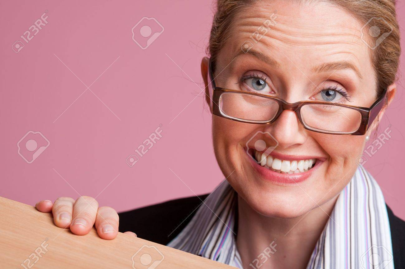Portrait of fun businesswoman behind desk on pink background Stock Photo - 6743476