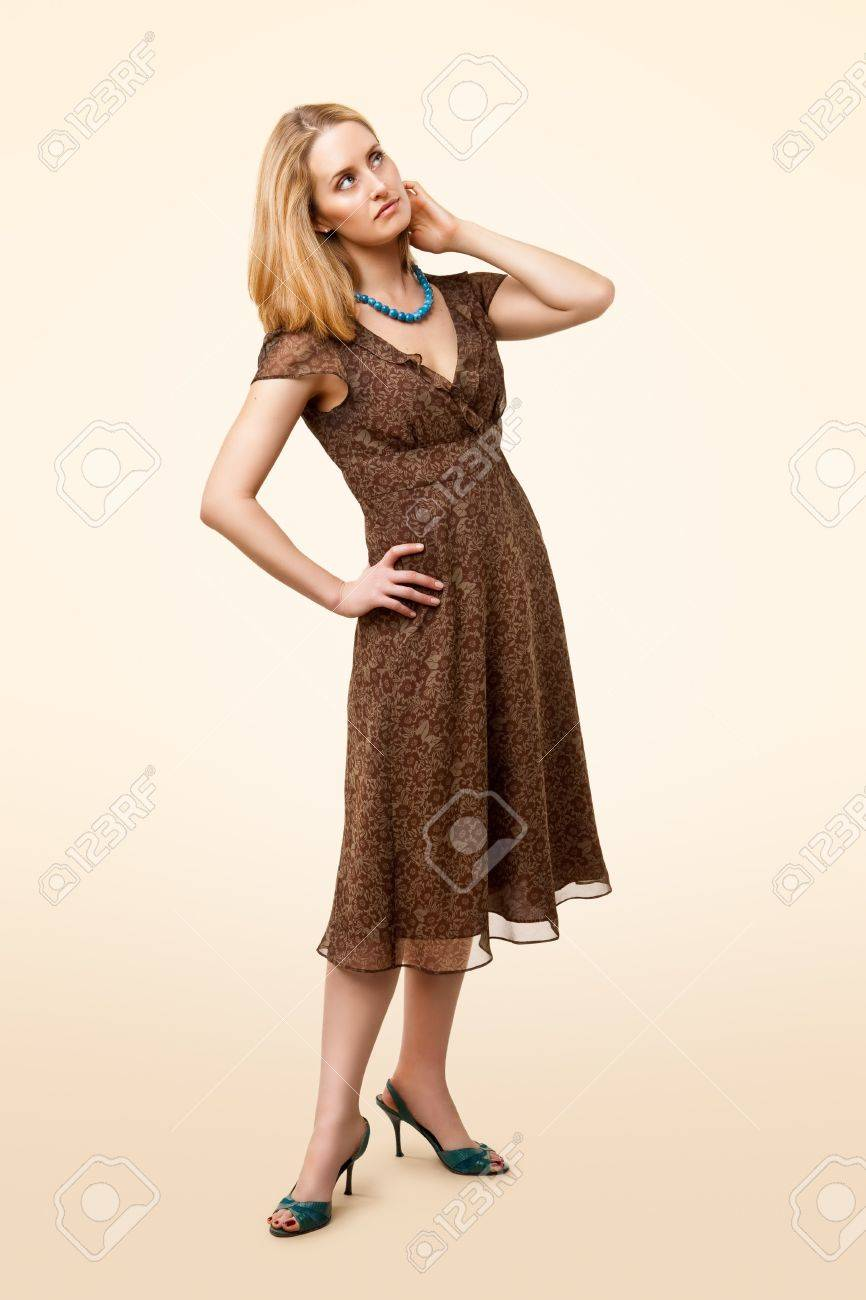 Full-length portrait of classic model wearing brown dress, standing and looking up Stock Photo - 7169485