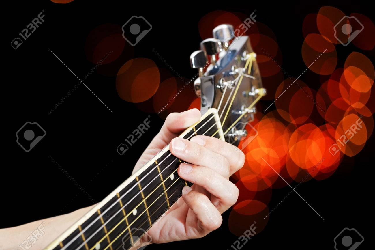 Man playing on acoustic guitar  Closeup fingers on guitar neck