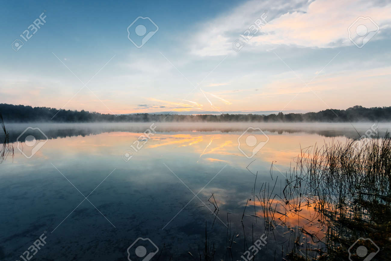 Beautiful, red dawn on the lake. The rays of the sun through the fog. The blue sky over the lake, the morning comes, the forest is reflected in the water. - 121933932