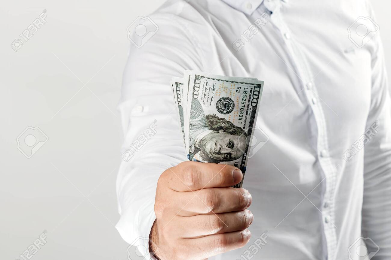 Money in the hands of a businessman, US dollars. The concept of corruption, pledge, bribery, fraud, auction bidding - 122099692