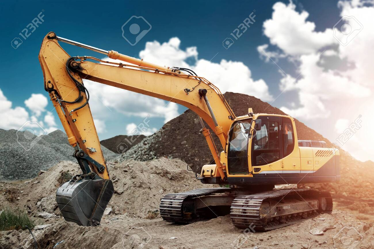 Excavator at the construction site, sand, crushed stone, against the blue sky background. Construction equipment, construction. - 122097908