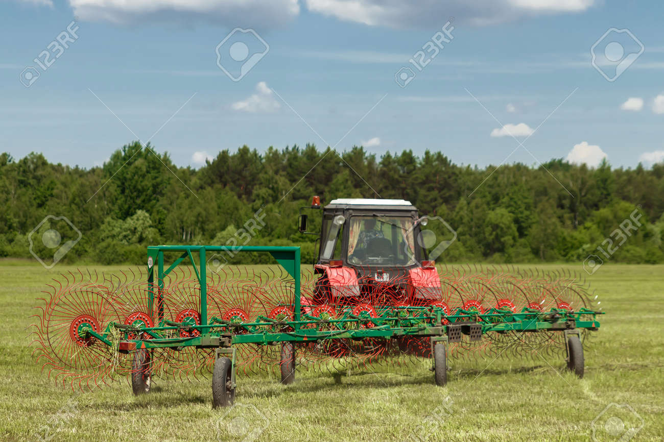 Agricultural machinery, a tractor collecting grass in a field against a blue sky. Hay harvesting, grass harvesting. Season harvesting, grass, agricultural land. - 122094213