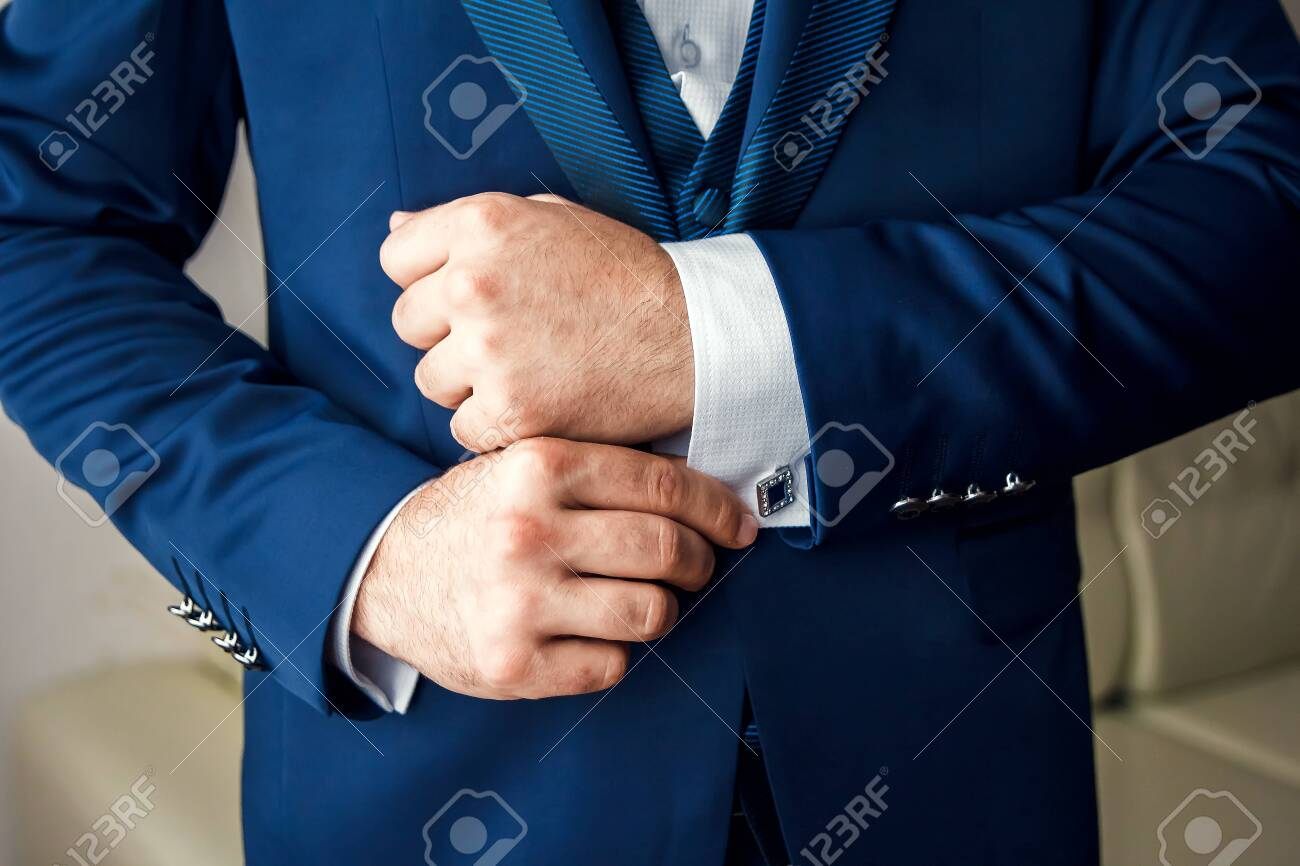 A man in a blue suit straightens his sleeves - 122993873