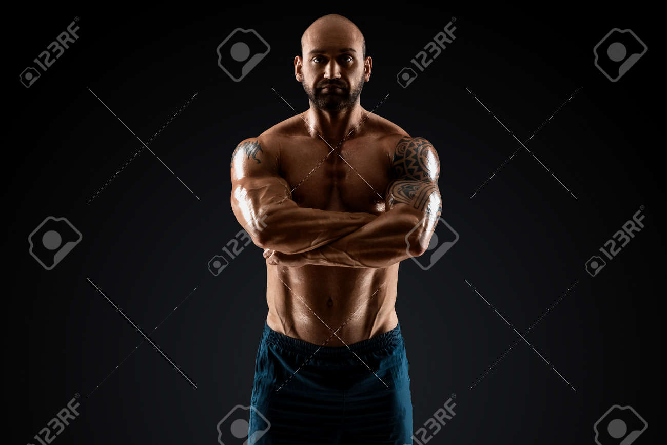 Male bodybuilder with light stubble with a torso posing against a dark background. The concept of a fitness club, doing sports, weightlifting. Copy space - 165746783