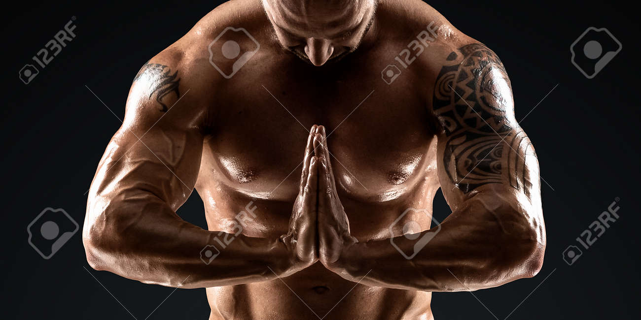 Male bodybuilder with light stubble and torso shows muscularity against a dark background. The concept of a fitness club, doing sports, weightlifting. Copy space - 165746807