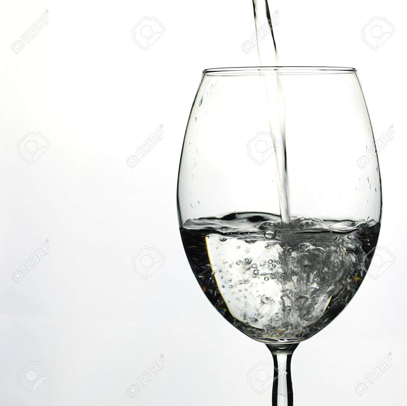 Pouring Water Into Wine Glass On White Background