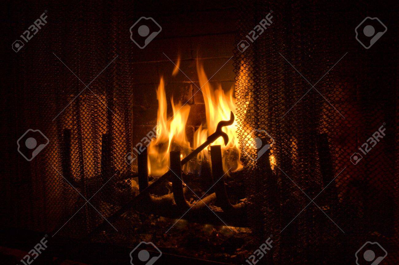 Fireplace Poker In Flames Of Fire Background Stock Photo Picture
