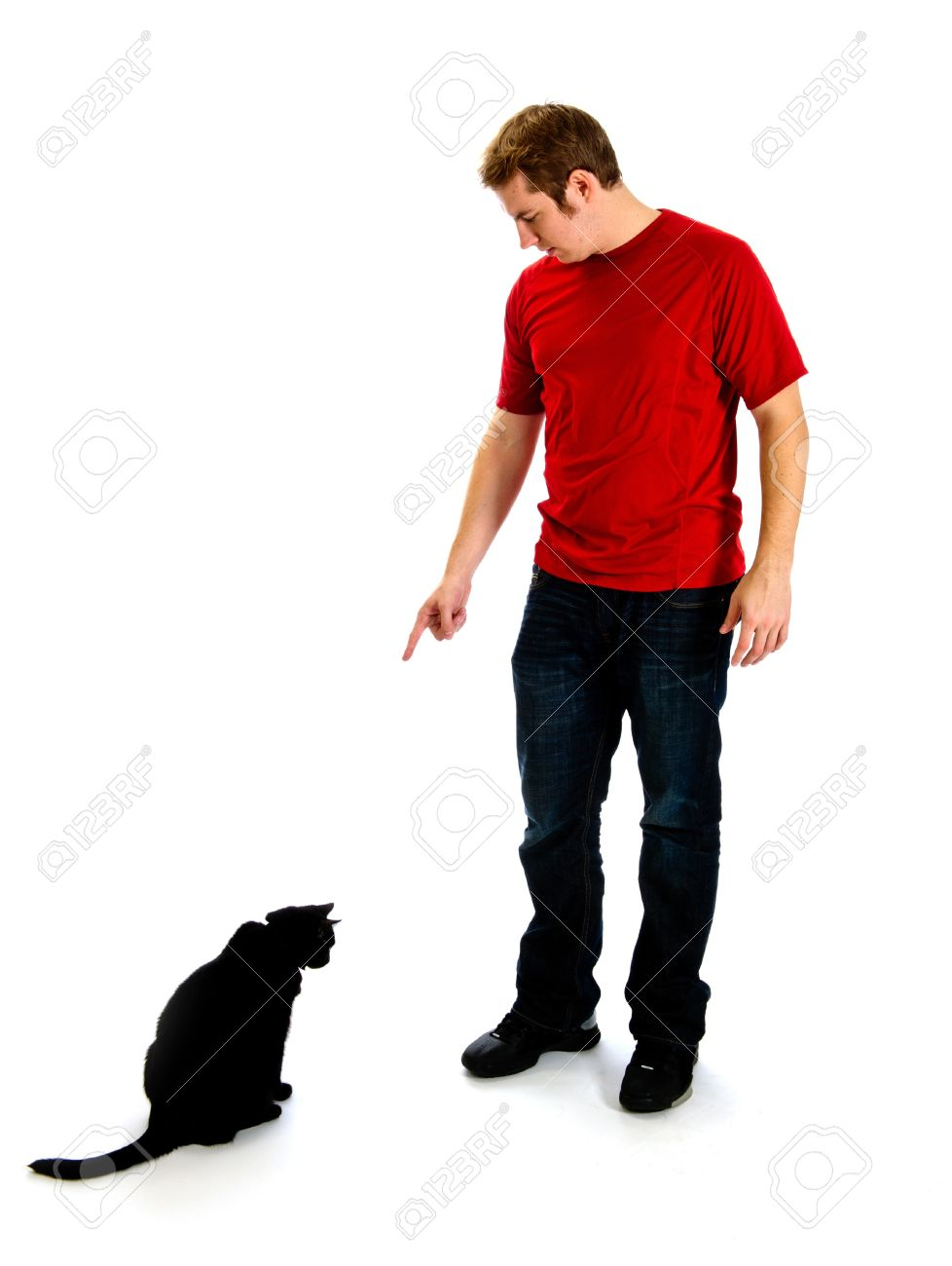 Young Man In A Red Shirt And Jeans, Is Pointing Down At A Black ...