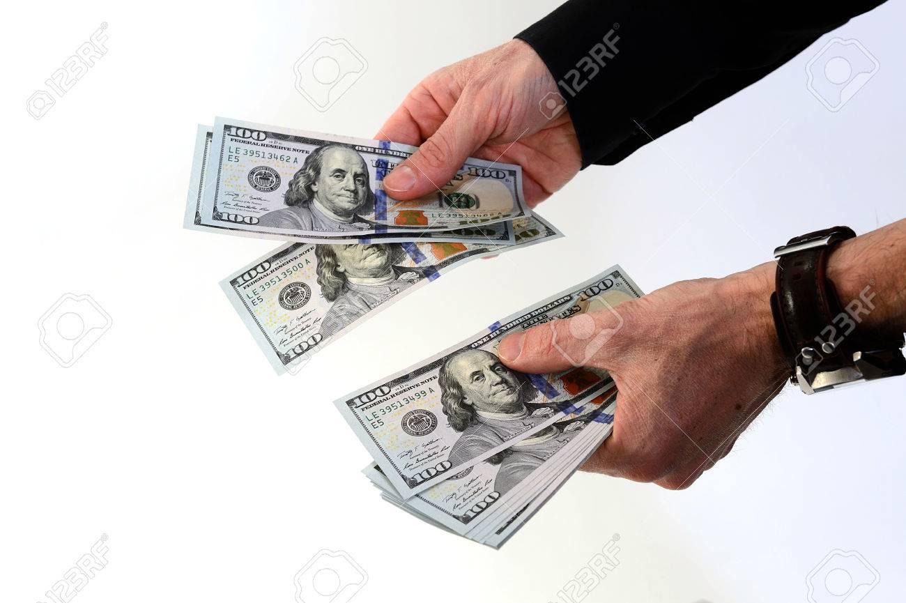 Person holding several new hundred dollar bills shot on white