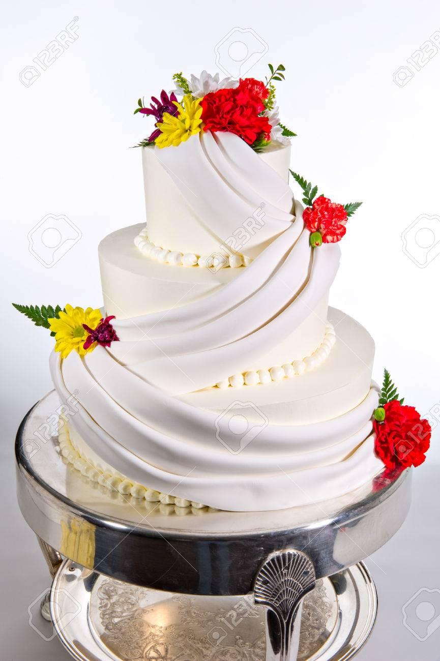 Fleurs Colorées Et Son Design Glace élaborée Ornent Ce Beau Gâteau De Mariage à Trois Niveaux Chaque Niveau Est De Forme Ronde Et A Tiré Sur Un Fond