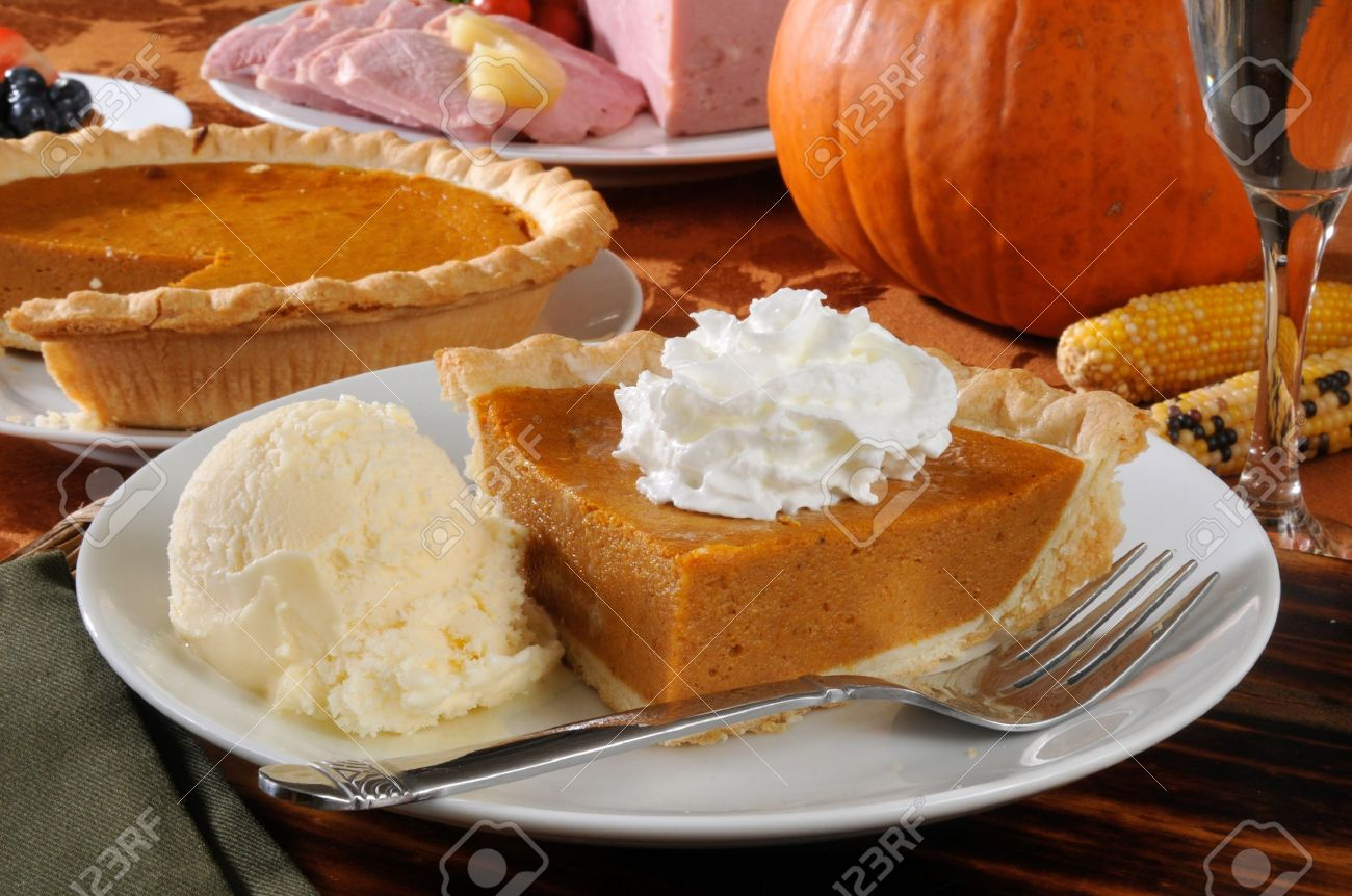 A Slie Of Pumpkin Pie With Ice Cream And Thanksgiving Dinner In The Background Stock