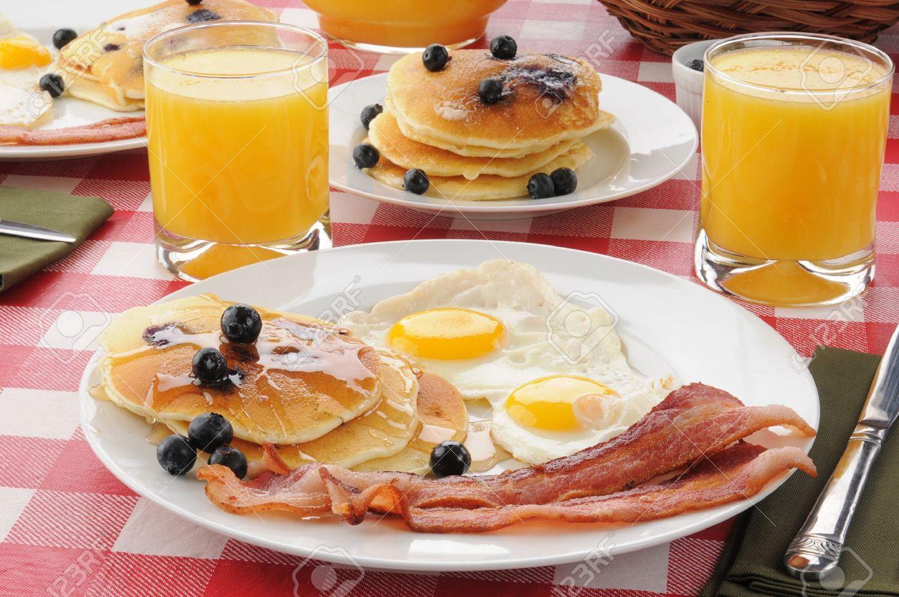 Un Desayuno Con Tocino Y Huevos Fritos Con Panqueques De Arándanos Y Jugo De Naranja Fotos Retratos Imágenes Y Fotografía De Archivo Libres De Derecho Image 14108295
