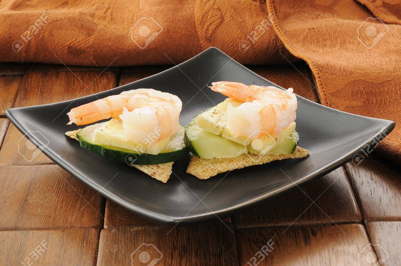 A plate of shrimp canapes with cucumber, dill cheese and crackers Stock Photo - 16211228