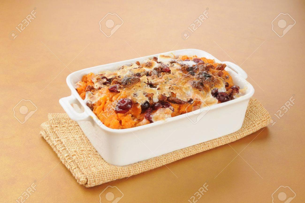 A dish of sweet potato casserole on a hot pad - 16747433