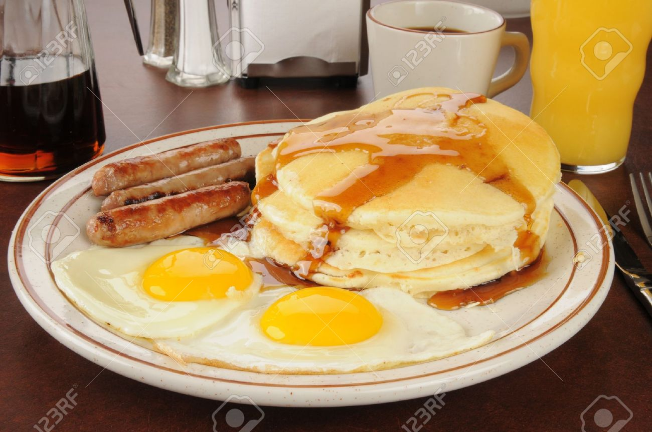 A sausage and egg breakfast with pancakes - 16818899