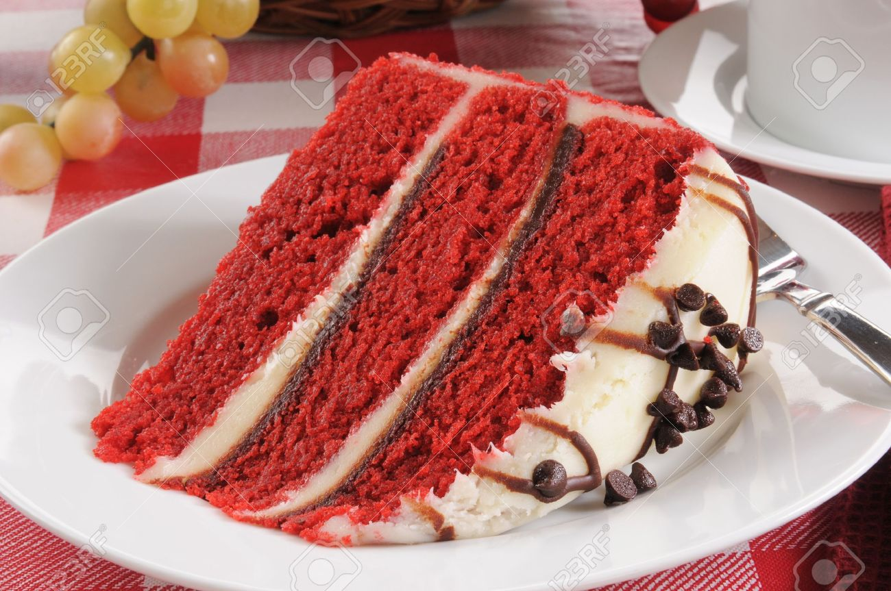 A slice of red velvet cake with chocolate chip icing - 18209225