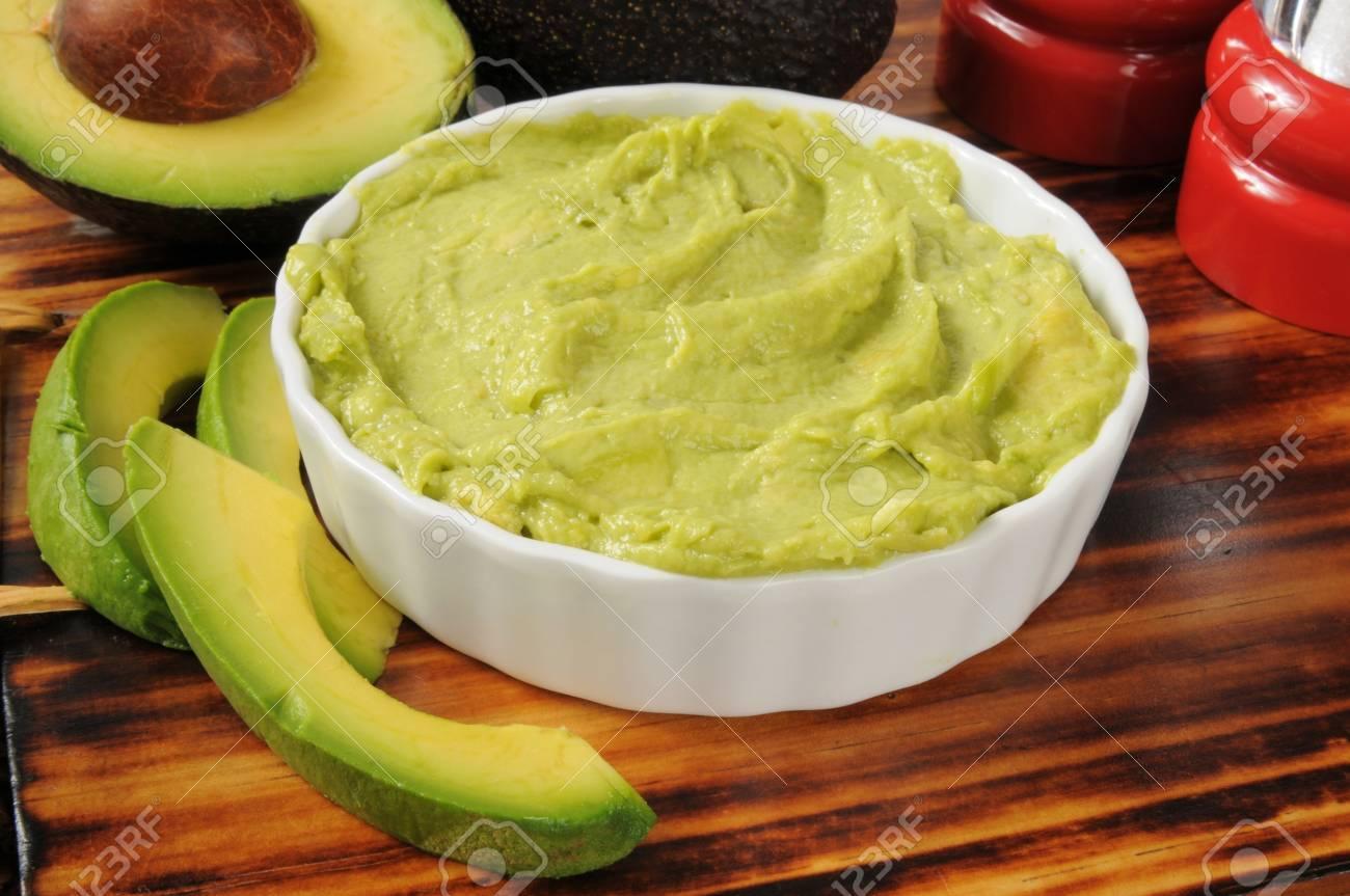 A bowl of fresh guacamole with fresh avocado - 21637966