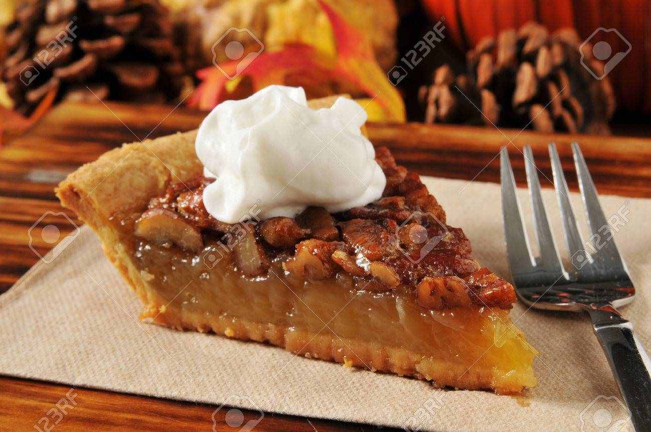 A slice of pecan pie on a holiday setting - 22801933