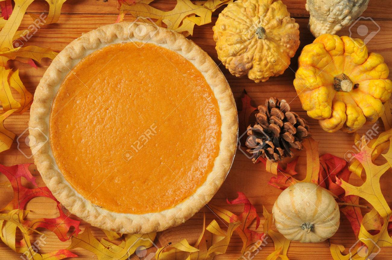 A whole sweet potato pie on an artistic set with autumn leaves, squash and gourds. - 22801941