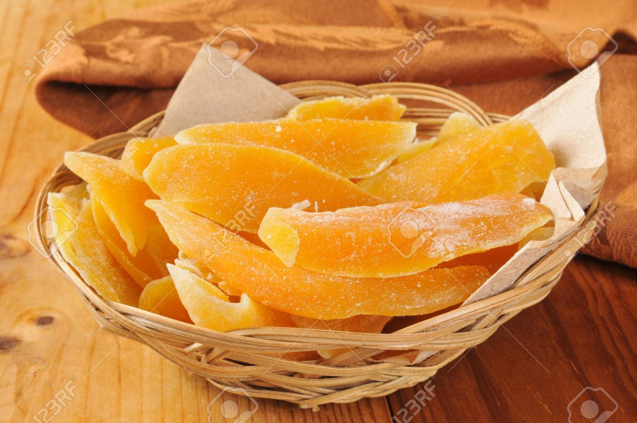 A basket of dried mango slices on a wooden table - 28757866