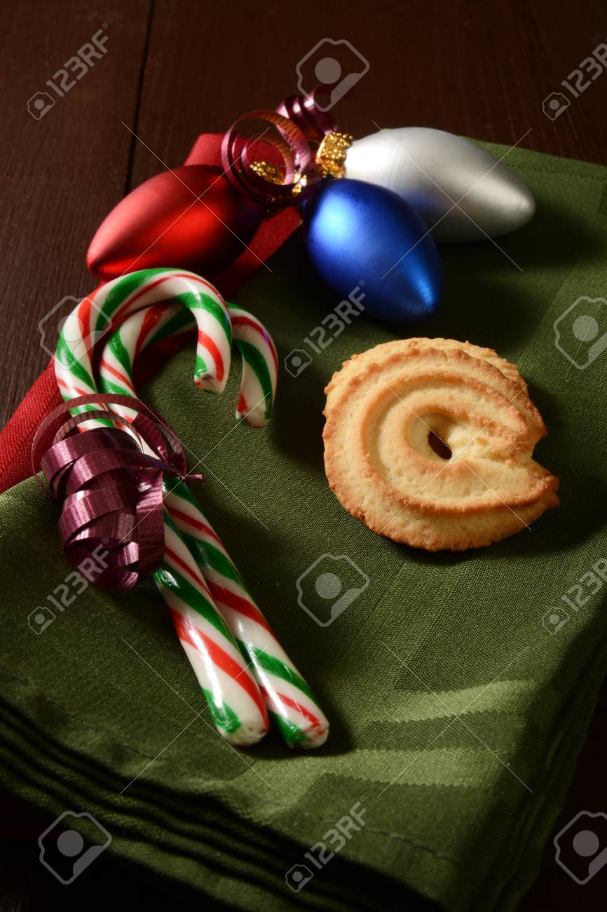 Butter Cookies And Candy Canes On A Napkin With Christmas Ornaments