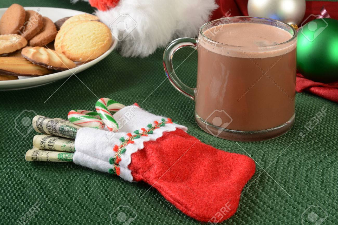 a small christmas stocking stuffed with money and candy canes stock