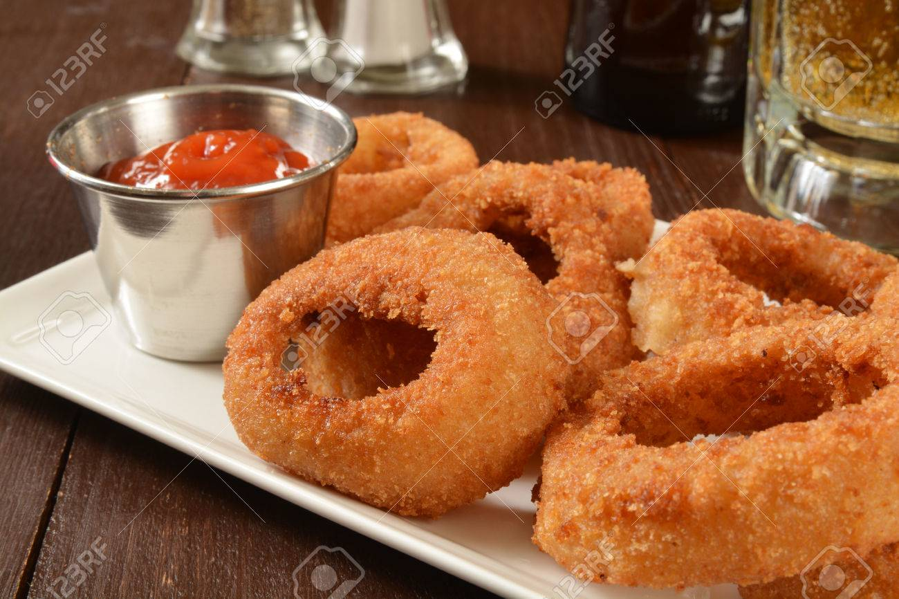 A plate of onion rings on a bar counter with a mug of beer - 38967405