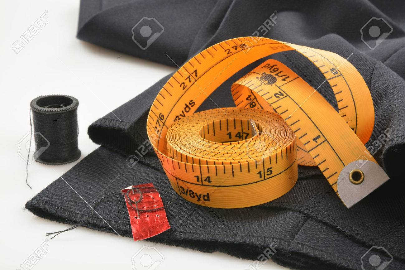 Needle and tread with a measuring tape on pants that need a hem put in - 38967407