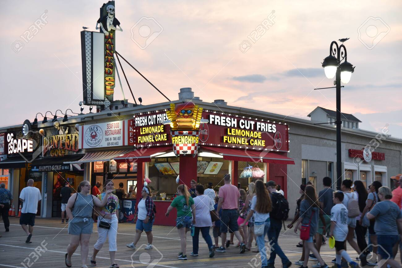 OCEAN CITY, NEW JERSEY/USA - JUNE 27, 2019: Tourists passing food stands and amusement arcades on the Ocean City Boardwalk at sunset - 136575794