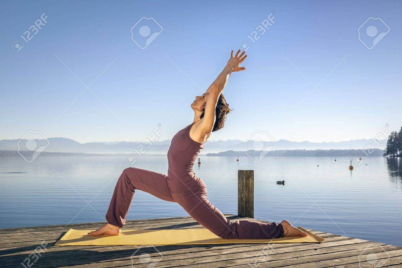 An image of a pretty woman doing yoga at the lake - 16374708