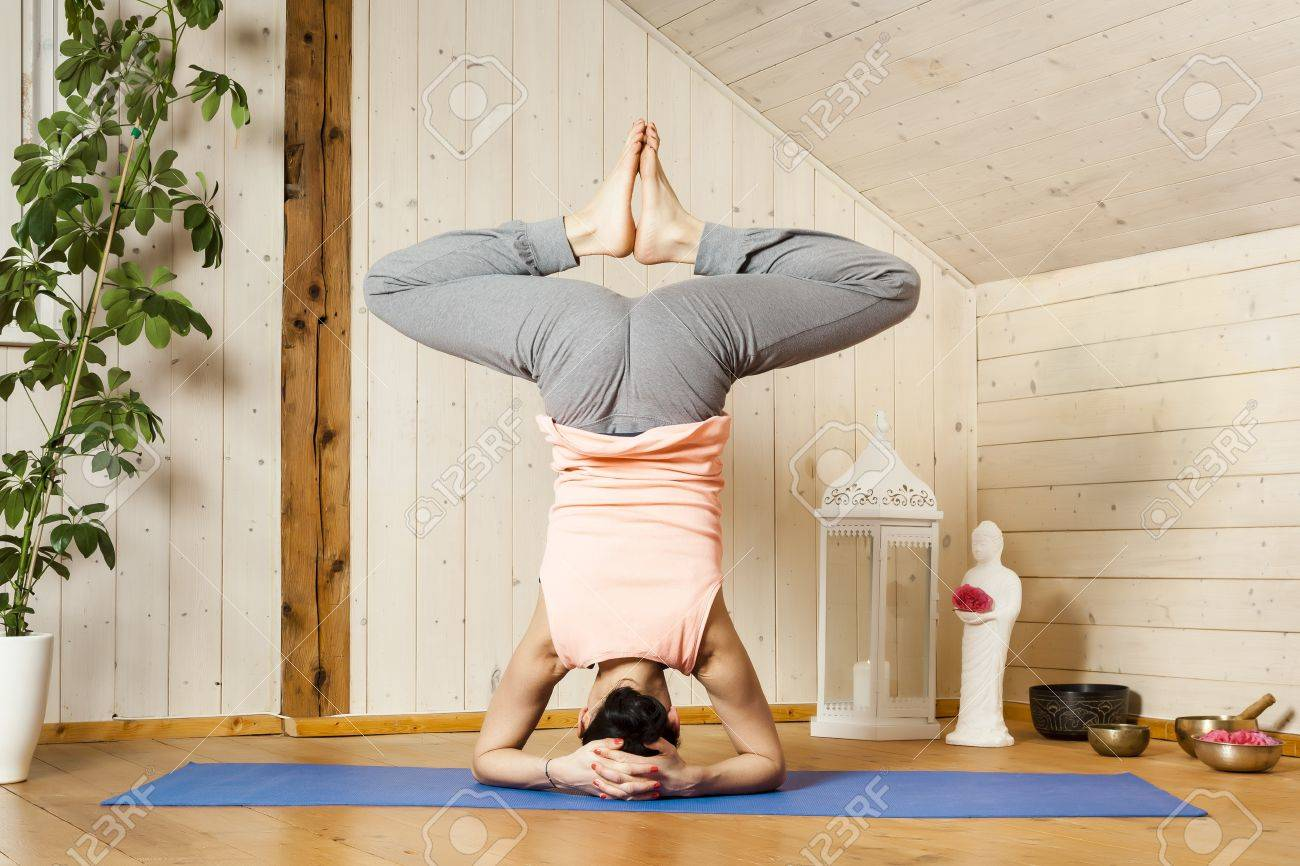 An image of a pretty woman doing yoga at home - Baddha Konasana Shirshasana Stock Photo - 18599424