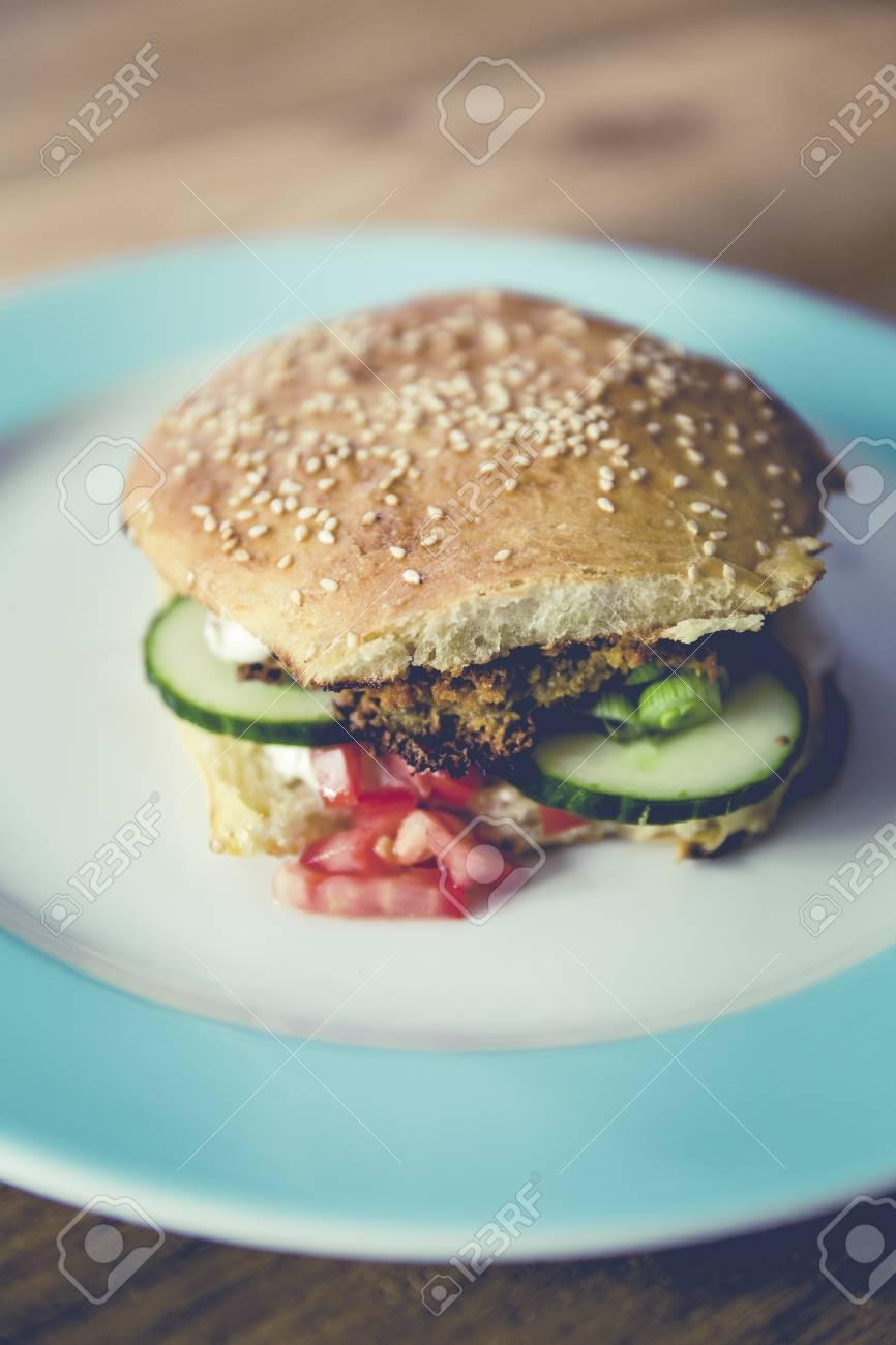 homemade veggie burger with cucumber, falafel, garbanzo, chickpea, tomato and wild celery Standard-Bild - 61502316