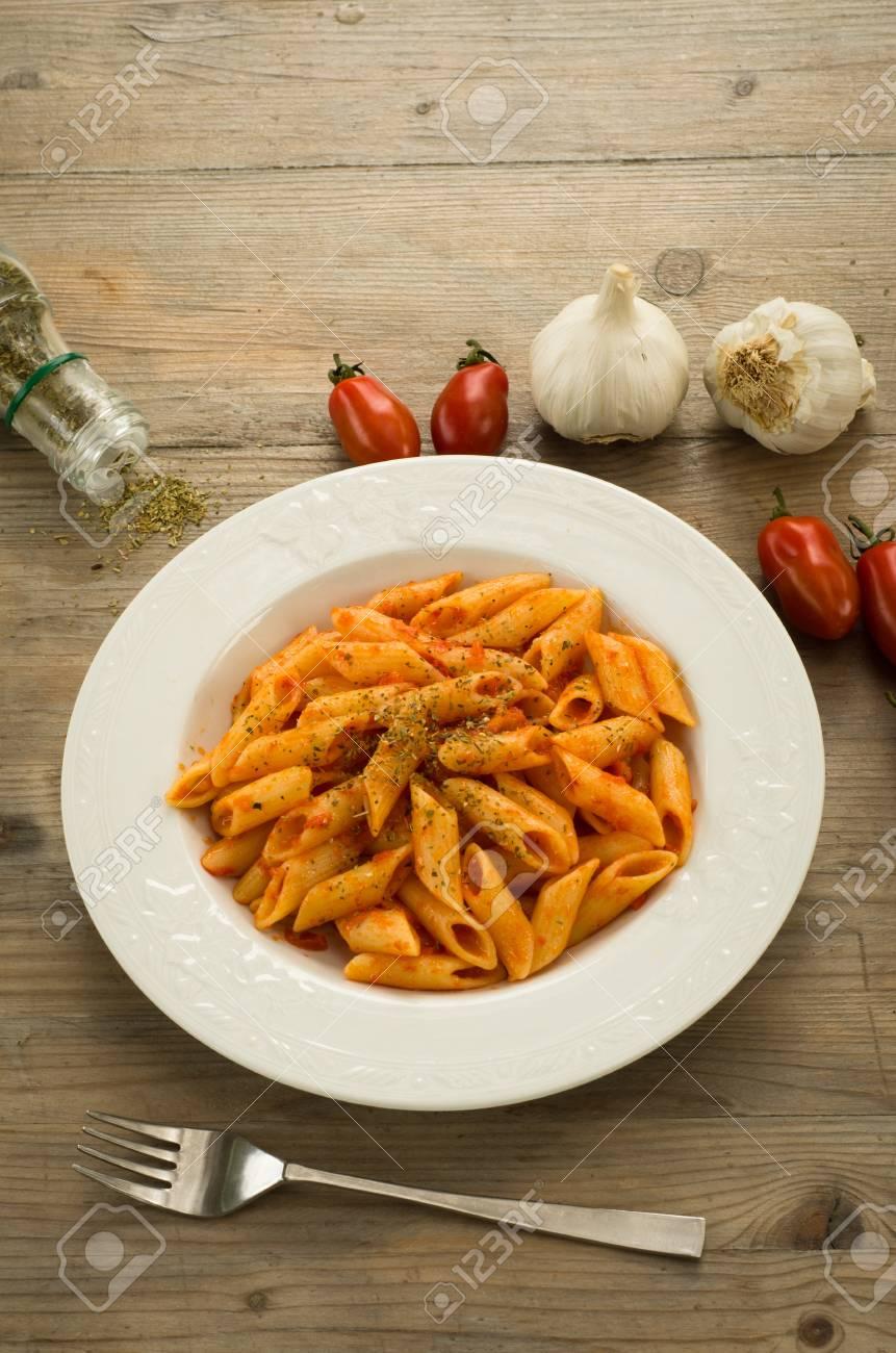 Penne pasta dressed with tomato sauce, garlic and oregano Stock Photo - 13756341