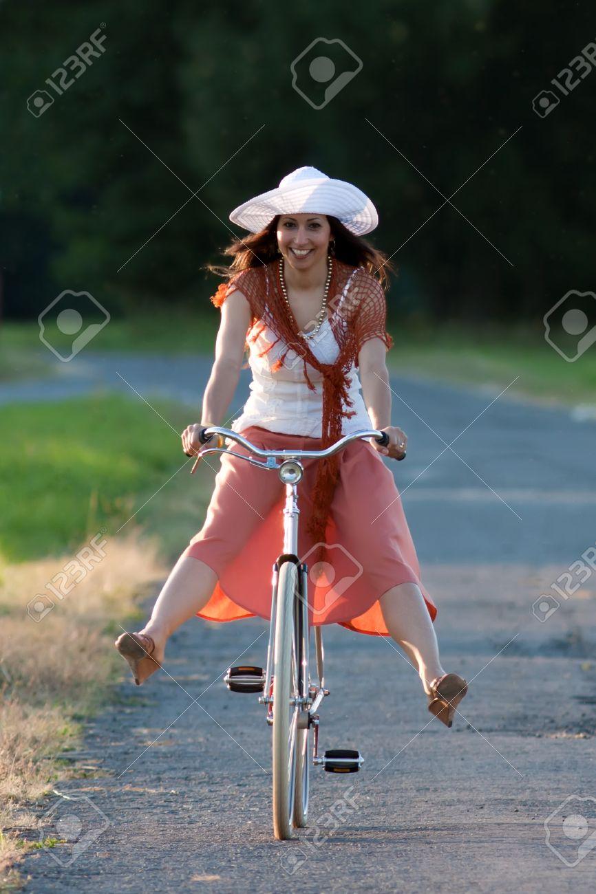 Femme Vélo Dans Blanc La Un Chapeau Cheval Orange À Jupe Et Sur 8PwO0nk
