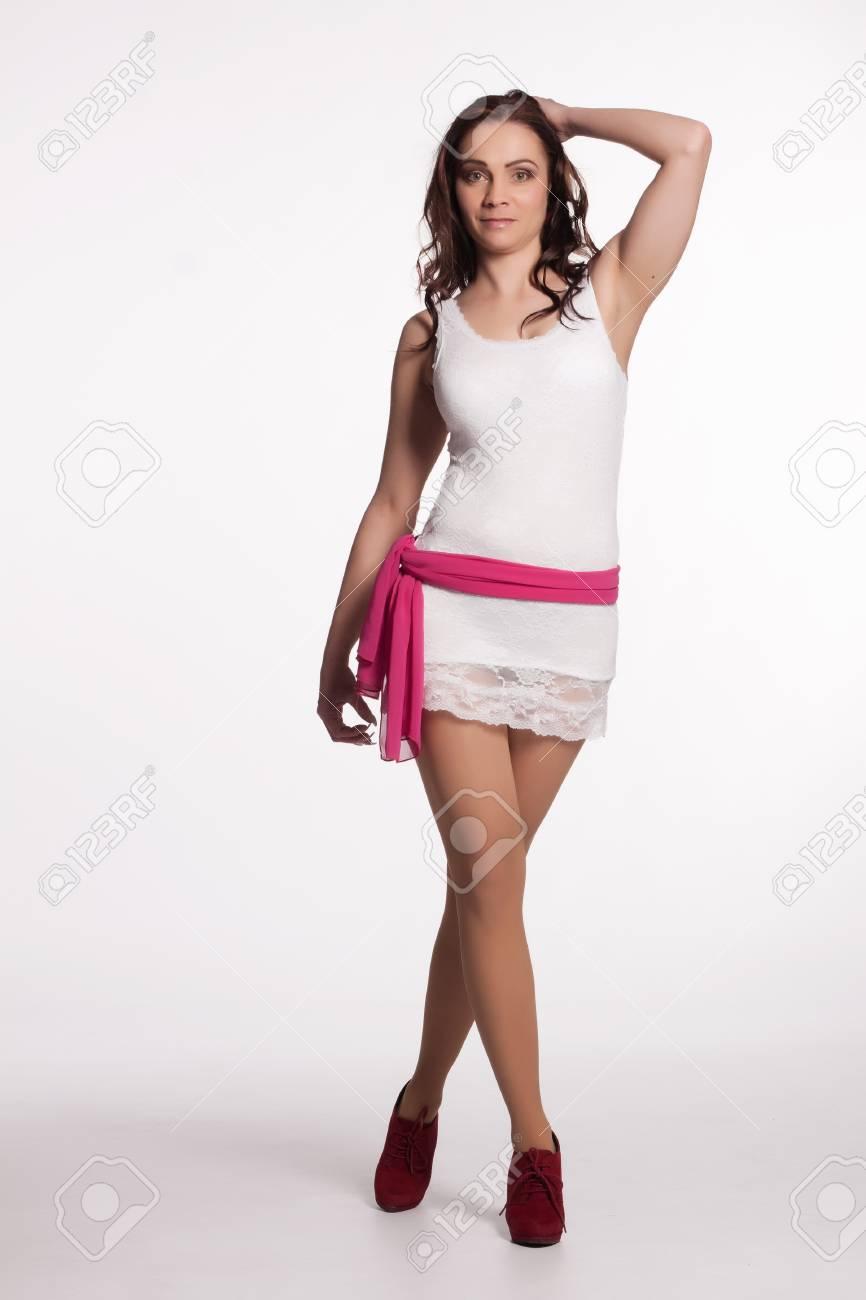 9ef79da9e Mujer joven en un mini vestido blanco, zapatos de tacón rojo posando con un  pañuelo de color rosa