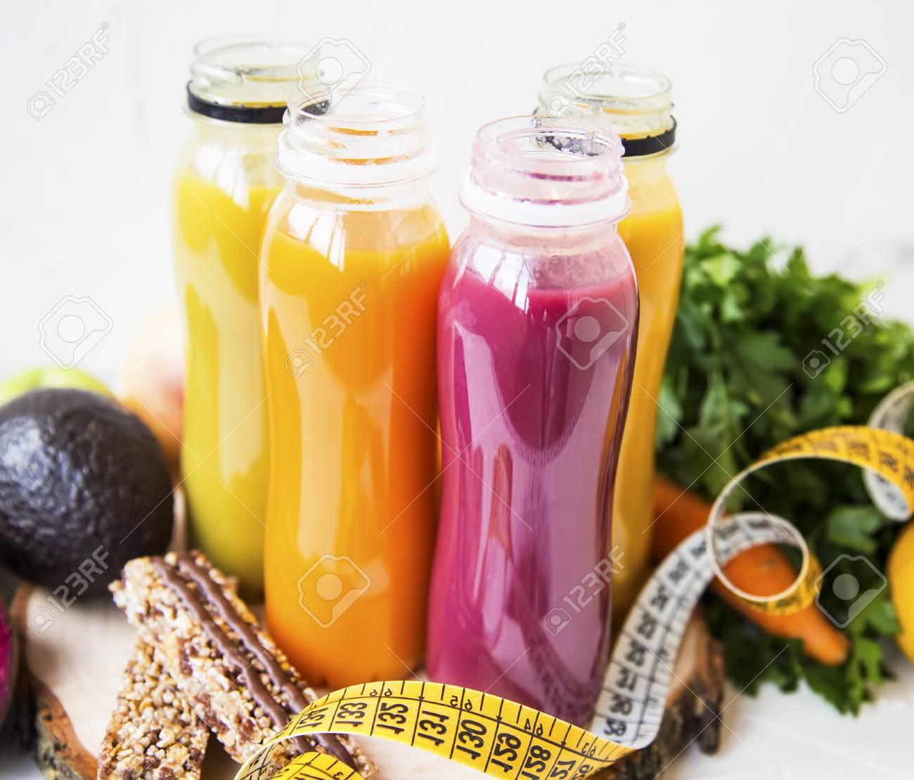 fresh organic juices in bottles, red, orange, yellow healthy..