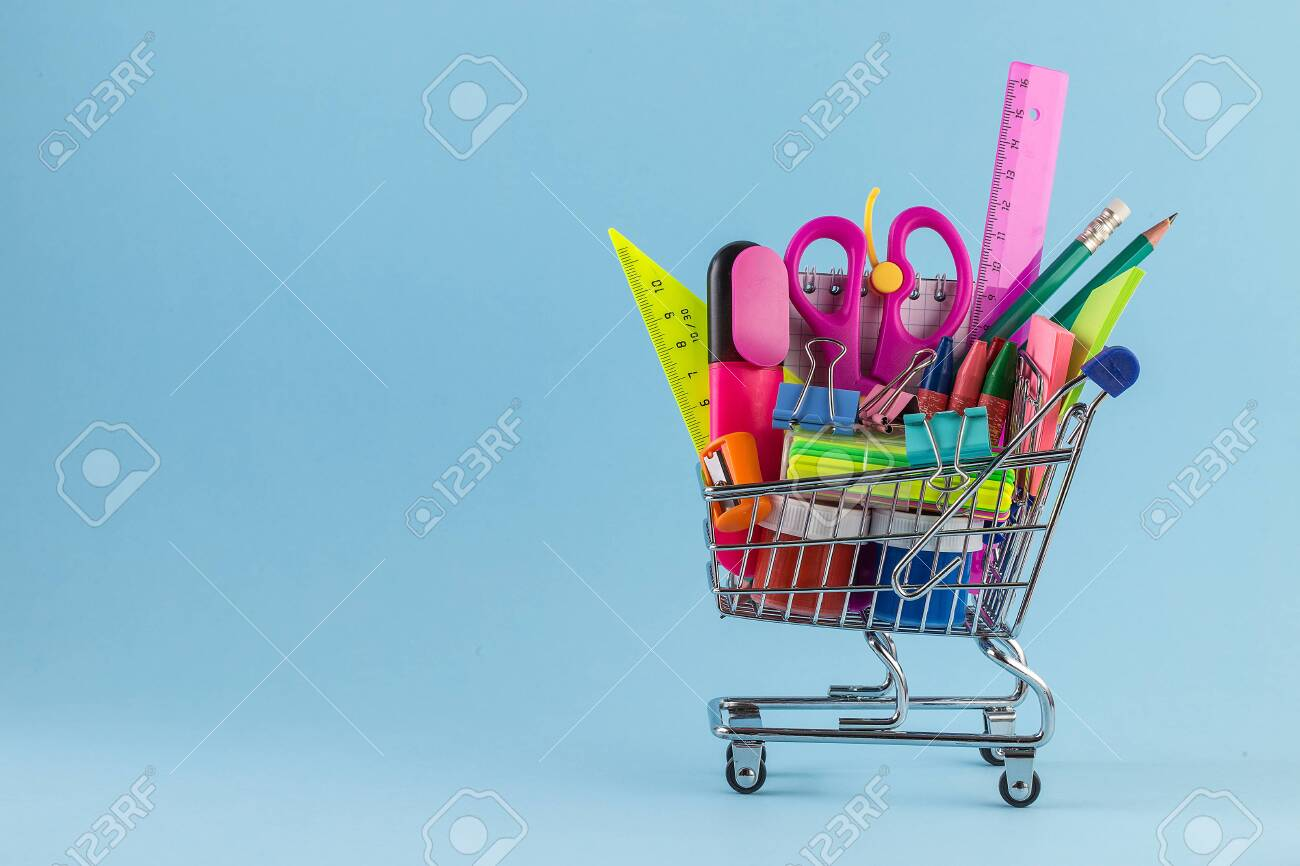Shopping cart with different stationery on the blue background. - 129263994