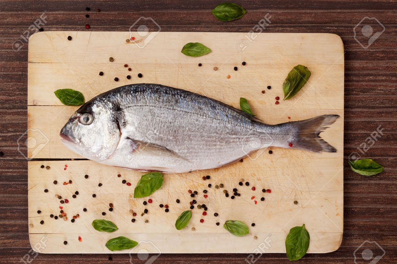 Sea bream on wooden chopping board with colorful peppercorns and basil leaves on brown background. Culinary seafood concept in natural brown. Stock Photo - 14841459