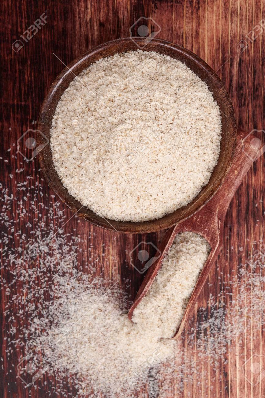Dietary fiber psyllium in round wooden bowl on dark brown wooden background - 26002394