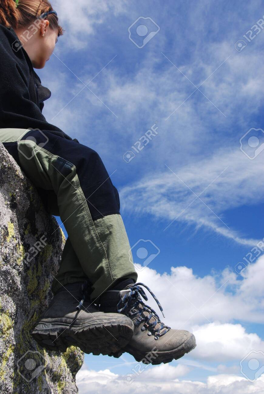 Hiking woman relaxing on rocks with blue sky Stock Photo - 3663435