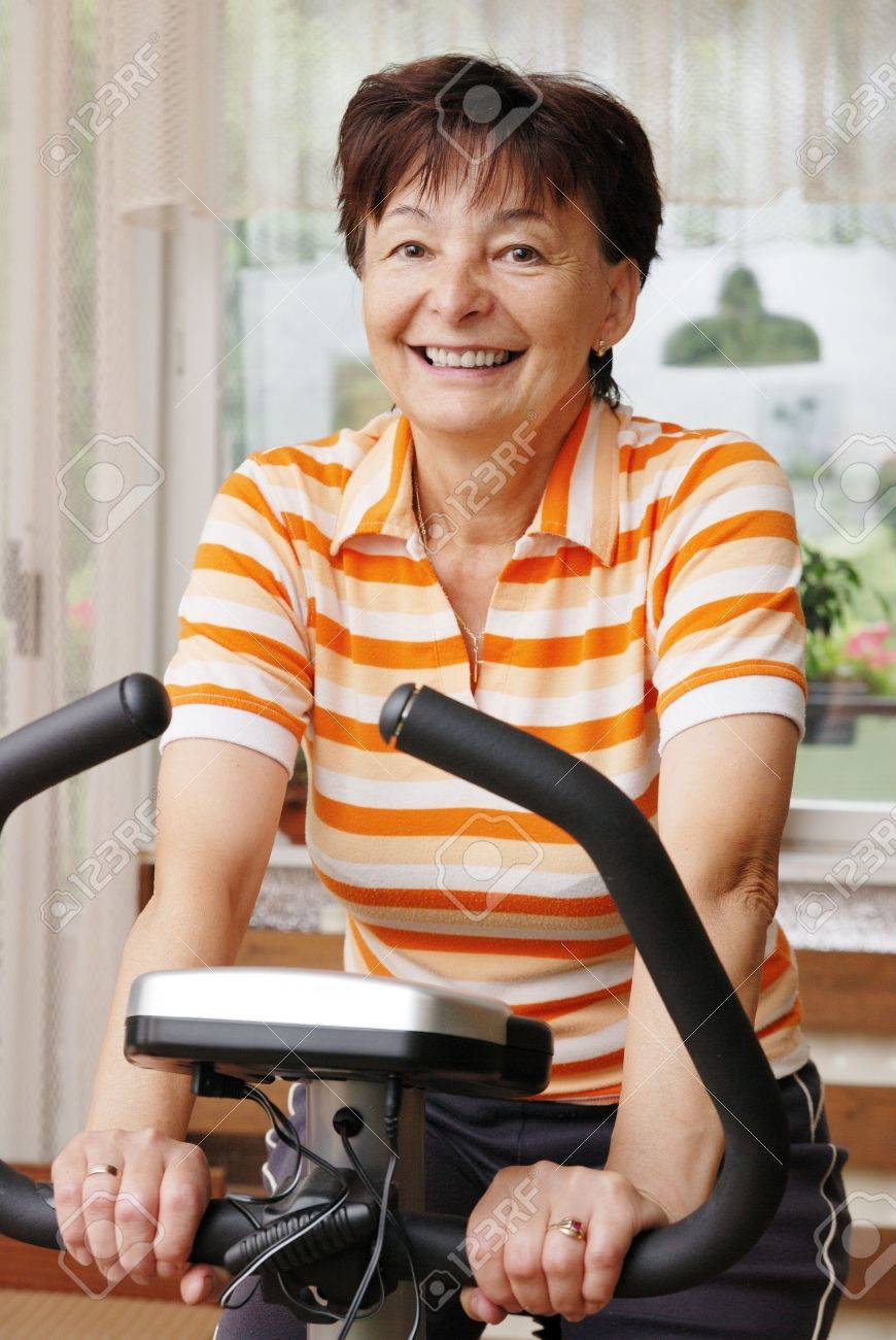 Mature woman exercise on spinning bicycle at home Stock Photo - 3674692