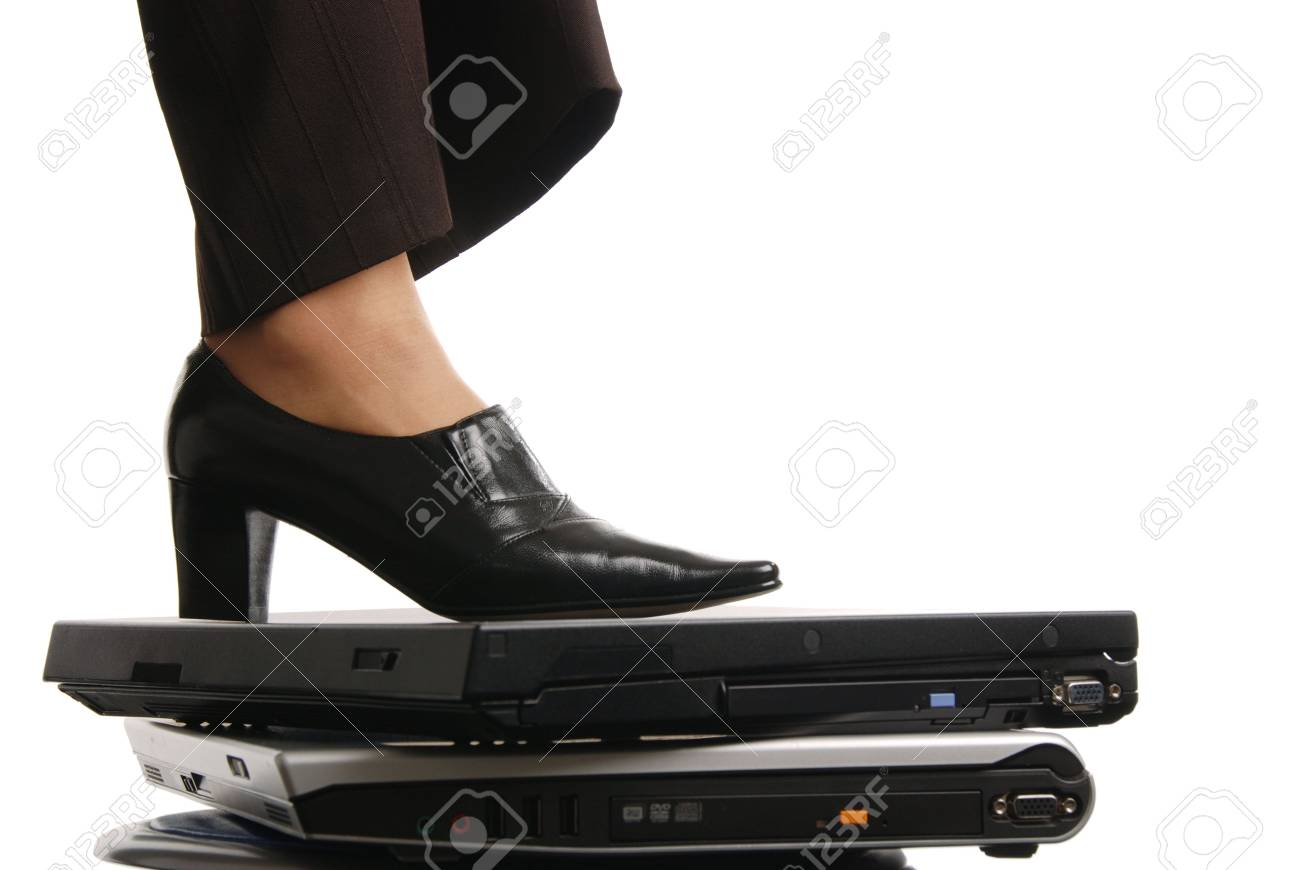Leg of woman in elegant shoe stands on computers - isolated on white background Stock Photo - 3830162