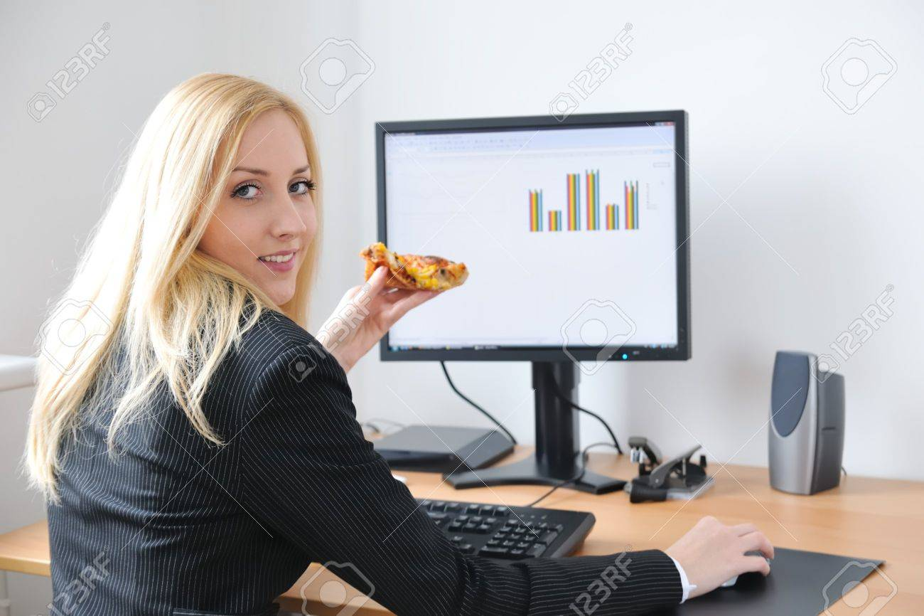 Young smiling business person working with computer eating pizza - 4534190
